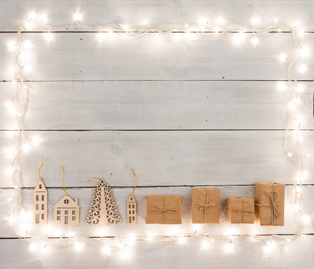 retro: christmas decoration on wooden table -  gift boxes, houses, tree, xmas lights and copy space for text