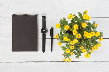 Notepad, watches, pen and flower vase on a wooden table