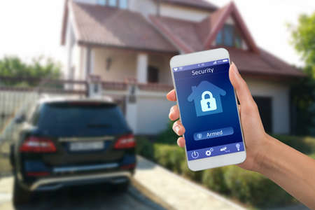 Smartphone with home security app in a  on the building
