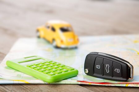 Car rental concept - car key and calculator on the road map Banque d'images
