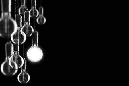Idea and leadership concept Vintage incandescent Edison type bulbs on black wall