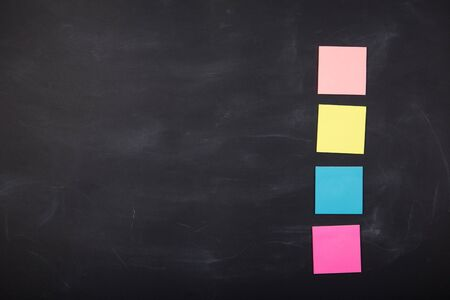 Colorful sticky notes on the blank blackboard Фото со стока