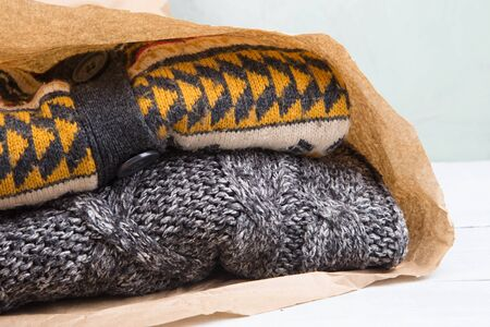 Shopping - warm sweaters in a paper bag on a wooden table