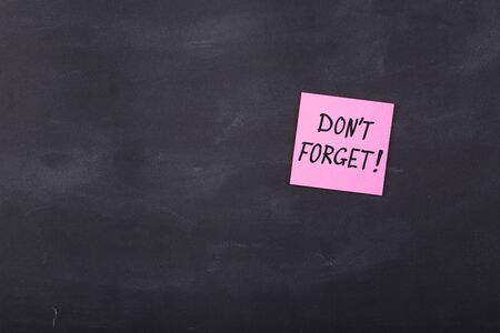 Don't forget inscription on colorful stickers on blackboard