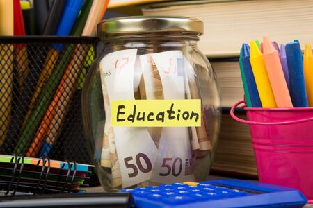 School supplies and glass jar with money for education on wooden table with open books Banque d'images