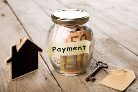 Rental payment concept - money jar, key with label and little house on the wooden desk