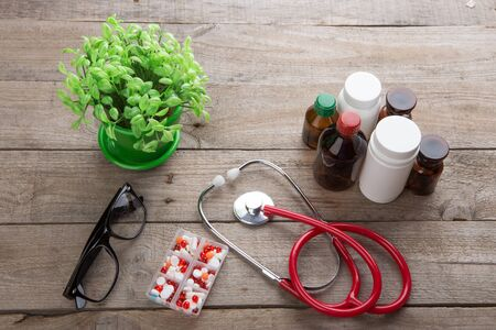 Workplace of a doctor. Stethoscope and drugs on the wooden desk
