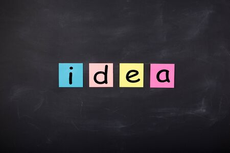 Business concept - Word 'Idea' written on color stickers on the chalkboard Banque d'images