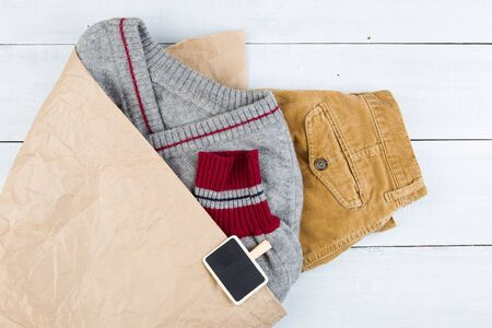 Shopping - warm sweater and pants in a paper bag and sale signboard, copy space for text