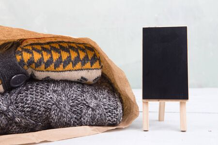 gifts - warm sweaters in a paper bag and sale signboard, copy space for text Banque d'images