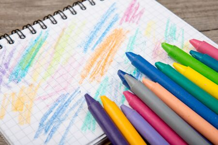 colored crayons and blank page on the wooden table
