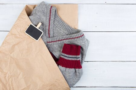 Shopping - warm sweater in a paper bag and sale signboard, copy space for text