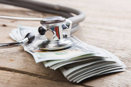 health insurance concept - stethoscope over the money on the table