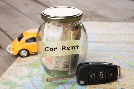 Car rental concept - car key and money jar on the road map