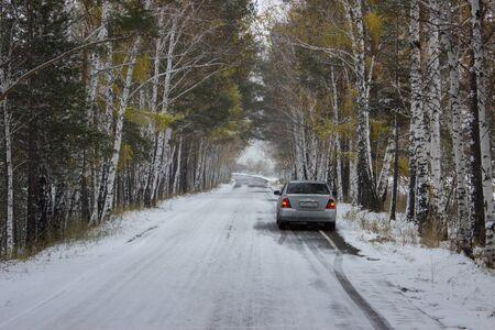 秋、雪に覆われた路地に車。ロシア、シベリア
