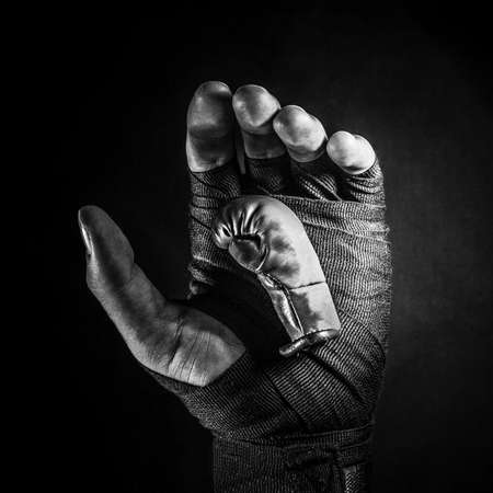 Red boxing glove in a man's hand on a black background.