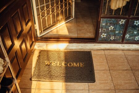 Welcome sign rug on the rustic stone floor at the front of the old door at sunset