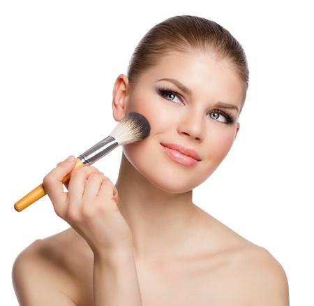 mujer maquillandose: Retrato de mujer sexy joven aplicar colorete atractivos ojos azules sonriente mujer con un pincel de maquillaje tocar su piel perfecta aislada sobre fondo blanco