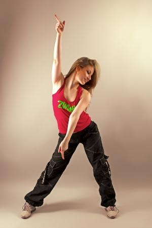 Young woman enjoying aerobics zumba fitness and raising her hand