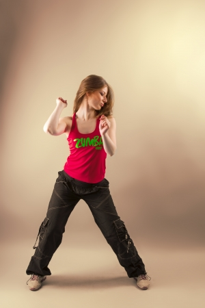 Aerobics  zumba fitness woman dancing in studio  Active, energetic, joyful aerobic instructor in motion photo