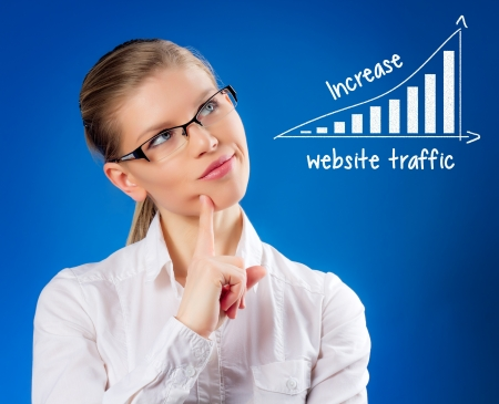website traffic: Seductive young woman in eyeglasses thinking about website traffic increase  SEO  online marketing concept  Beautiful blond female looking at SEO chart  Stock Photo