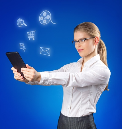 devise: Pretty young lady looking at social media icons  Attractive blond in business style in eyeglasses holding tablet PC in her hands