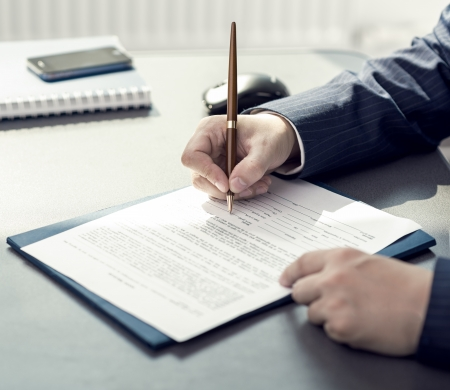 financial agreement: Financial planning specialist signing annual report in office