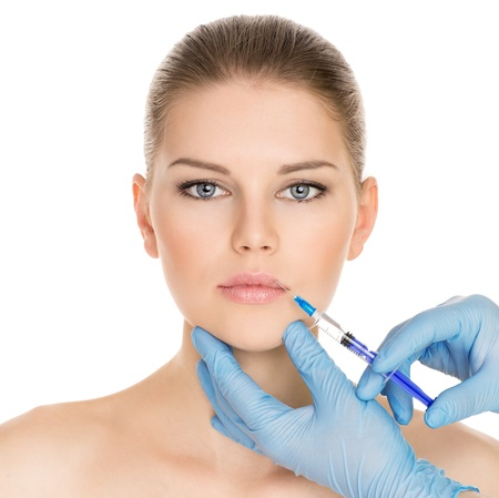 Portrait of young Caucasian woman getting cosmetic injection of botox, isolated over white background
