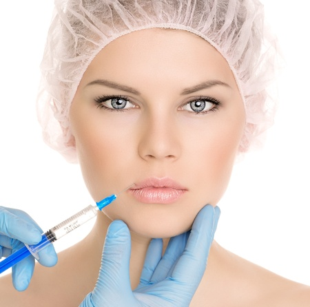 injections: Beautiful woman getting cosmetic injection in lips, isolated over white background  Nice attractive blonde model in medical cap  Stock Photo