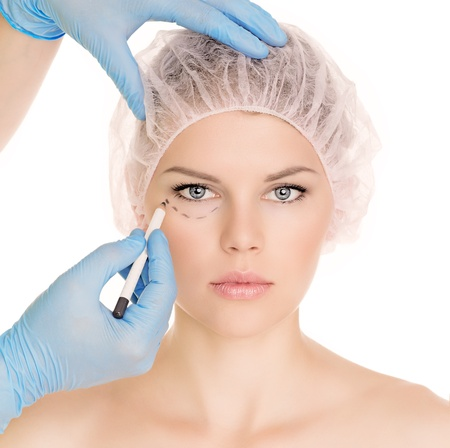 plastic glove: Plastic surgeon drawing lines over eyelid of a nice young female before cosmetic operation, isolated over white background