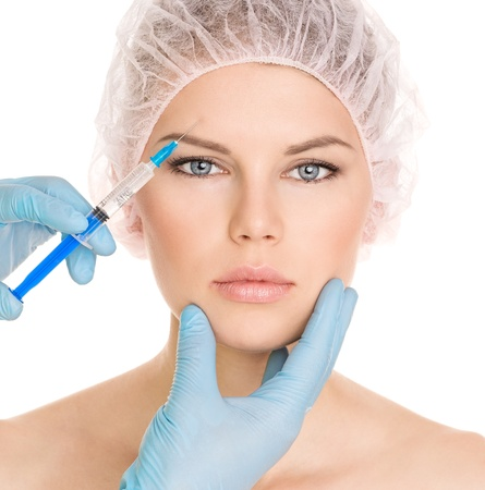 face lift: Cosmetic injection in brow zone, isolated on white background  Young pretty blue eyed female in medical cap