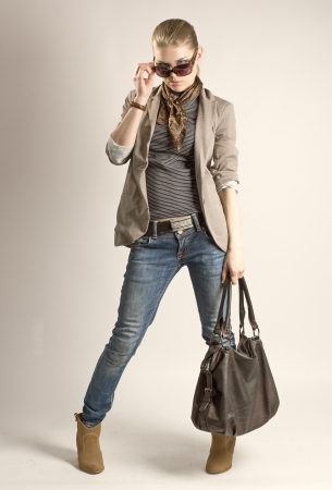fashion bag: Fashionable shopping girl  Sexy blond Caucasian female in sunglasses holding leather bag  Stock Photo