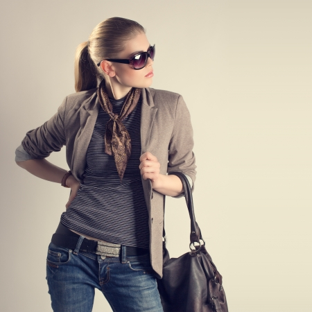 aside: Shopping woman  Attractive young Caucasian fashion girl in sunglasses holding a leather bag and looking aside