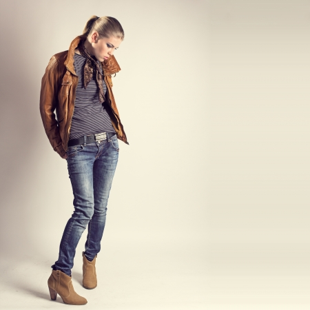 charmingly: Fashion girl  Beautiful glamour stylish model in leather jacket, neckerchief, jeans, high heels  Young Caucasian woman posing in studio  Stock Photo