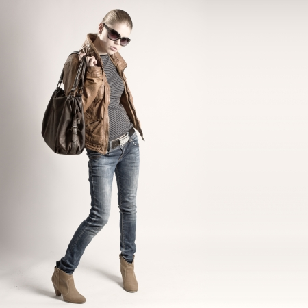 jeans girl: Fashionable young girl dressed stylish and modern in leather jacket, jeans with big bag  Blond Caucasian shopping woman in sunglasses