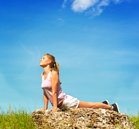 find similar images:   Save to a Lightbox   9660;    Find Similar Images    Share   9660; Yoga woman posing on the stone over sky background  Nice blond female traveler on the top of the hill in yoga pose  Stock Photo