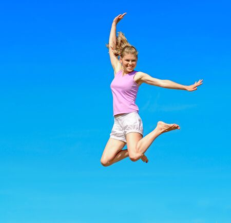 cliff jumping: Happy smiling Caucasian woman jumping over sky background  Stock Photo