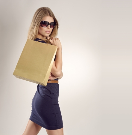 Glamour blonde lady in sunglasses with a shopping bag photo