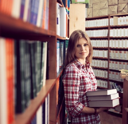 Successful commerce woman in proper book shop standing with books