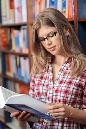 book shop: Portrait of young female in book shop reading book Stock Photo