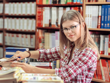 Beautiful young blond Female in library putting books in order photo