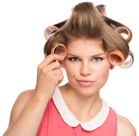 hair curler: Shoot of confused female in curlers thinking about curly hairdo  Beautiful blond Caucasian woman Isolated on a white  Stock Photo