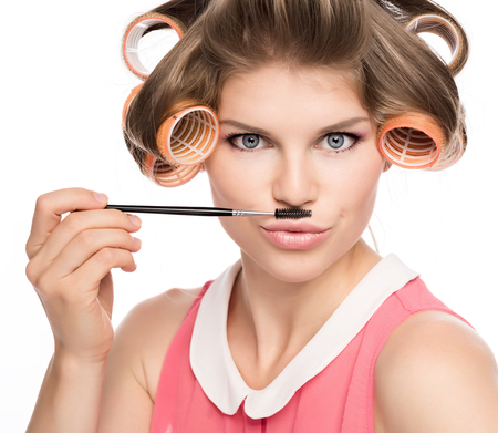 hair curler: Funny picture of beautiful female in curlers with mustache, isolated on white  Cute Caucasian woman in studio