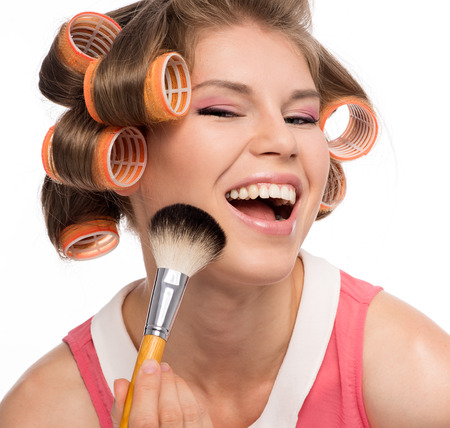 hair curler: Portrait of young cheerful female in curlers applying rouge with makeup brush  Beautiful blond Caucasian female happy smiling, isolated on a white background  Stock Photo