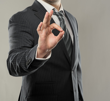 ok sign: Young successful businessman showing ok symbol  Close-up of entrepreneur s hand, studio shoot