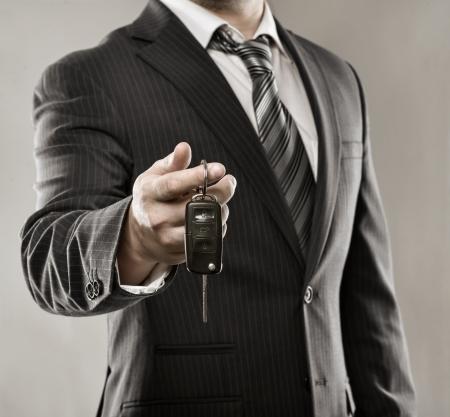 rental: Exitoso hombre de negocios joven que ofrece una llave de coche Primer plano de la mano del conductor s muestra clave de su propio autom�vil