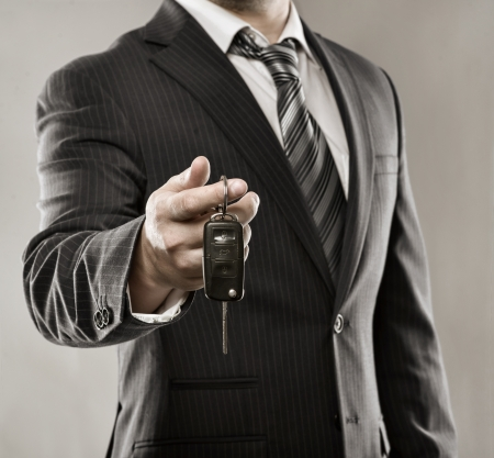 Young successful businessman offering a car key  Close-up of driver s hand showing key of his own automobile  photo