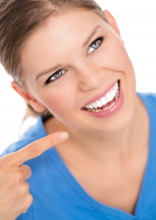 dentition: Happy dentistry woman showing white healthy teeth with her finger  Portrait of young pretty Caucasian female smiling with open mouth, isolated on a white background  Stock Photo