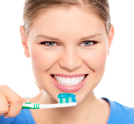 brush teeth: Happy woman showing her perfect white teeth holding brush  Young cheerful Caucasian female model in studio, isolated over white background  Stock Photo
