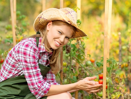 horticulturist: Happy horticulturist woman in straw hat in the backyard of the house  Young attractive Caucasian female gardener holding ripe vegetables